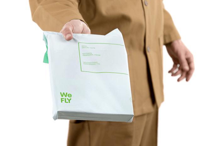 Una fattorino tiene in mano una WeFLYBIO, buste per spedizioni biodegradabili